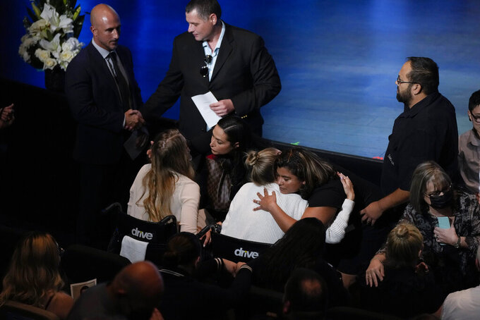Angela Gonzalez, center, and daughter Deven, left, both seated in wheelchairs due to their injuries, are embraced by well-wishers ahead of the funeral service for their late husband and father Edgar Gonzalez, 44, who was killed last month in the Champlain Towers South condominium collapse, on Friday, July 23, 2021, at Christ Fellowship church in Palmetto Bay, Fla. Angela and Deven were injured but survived the collapse, falling multiple stories. (AP Photo/Rebecca Blackwell)