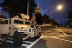 A member of the Georgia National Guard sits on a vehicle outside the State Capitol on Tuesday, July 7, 2020, in Atlanta. Georgia Gov. Brian Kemp mobilized the guard after an increase in gun violence over the weekend. (AP Photo/John Bazemore)