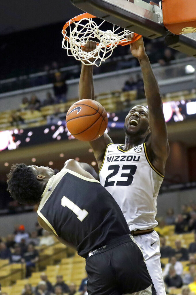 Missouri's Jeremiah Tilmon (23) dunks over Wofford 's Chevez Goodwin (1) during the second half of an NCAA college basketball game Monday, Nov. 18, 2019, in Columbia, Mo.  (AP Photo/Jeff Roberson)