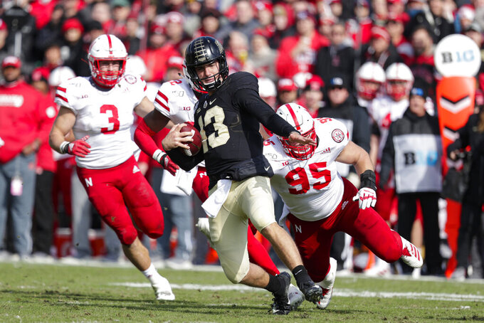 Purdue quarterback Jack Plummer (13) slides to a gain in front of Nebraska linebacker Will Honas (3) and defensive lineman Ben Stille (95) during the first half of an NCAA college football game in West Lafayette, Ind., Saturday, Nov. 2, 2019. (AP Photo/Michael Conroy)