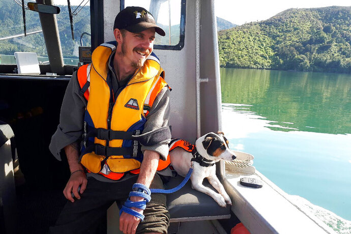 In this undated photo released by New Zealand Department of Conservation, Flint, the rat-detecting dog and its handler Richard Johnston ride on a boat near the Tennyson Inlet Islands in New Zealand. Flint was on a remote island between New Zealand and Antarctica as part of a mission involving the military when a sealion charged at him. He got spooked and ran away, and couldn't be found by a military helicopter. The team was forced to leave him behind on Wednesday, Nov. 27, 2019. But he was rescued on Friday, Nov. 29 after a helicopter crew flew to the island and found he'd walked back to the base.  (New Zealand Department of Conservation via AP)