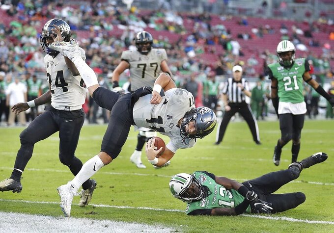 Central Florida quarterback Dillon Gabriel (11) leaps into the end zone for a touchdown over Marshall safety Nazeeh Johnson (13) during the Gasparilla Bowl NCAA college football game Monday, Dec. 23, 2019, in Tampa, Fla. (Stephen M. Dowell/Orlando Sentinel via AP)