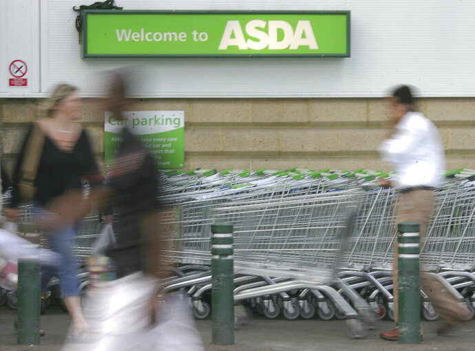 FILE - In this Tuesday July 17, 2007 filer, shoppers enter the Asda supermarket in Wallington, England. Retail giant Walmart has agreed to sell its British chain of supermarkets, Asda, to the investors behind an international group of gas stations and food shops in a deal that values the company at 6.8 billion pounds ($8.8 billion). Brothers Mohsin and Zuber Issa, along with investors TDR Capital will acquire a majority of Asda, while Walmart will retain a minority stake and a seat of the board, the parties said in a joint statement issued Friday. Details of the deal weren't released. (AP Photo/Tom Hevezi, File)