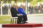 German Chancellor Angela Merkel sits alongside Britain's Prime Minister Boris Johnson during a welcome ceremony with military honors for a meeting at the Chancellery in Berlin, Germany, Wednesday, Aug. 21, 2019.( J'rg Carstensen/dpa via AP)