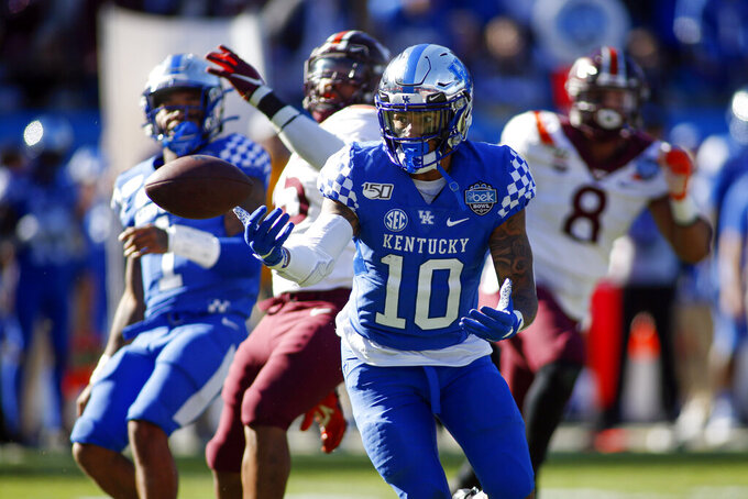 Kentucky running back Asim Rose (10) fumbles the ball against Virginia Tech in the first half of the Belk Bowl NCAA college football game in Charlotte, N.C., Tuesday, Dec. 31, 2019. He recovered the fumble. (AP Photo/Nell Redmond)