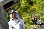 Amy Caspari, second from right, and her daughter Ana Gray, 12, right, watch as beekeepers Sean Kennedy, left, and Erin Gleeson, second from left, prepare to capture a swarm of honey bees and relocate them to a bee hive, Friday, May 1, 2020, in Washington. The District of Columbia has declared beekeepers as essential workers during the coronavirus outbreak. If the swarm isn't collected by a beekeeper, the new hive can come to settle in residential backyards, attics, crawlspaces, or other potentially ruinous areas, creating a stinging, scary nuisance (AP Photo/Andrew Harnik)