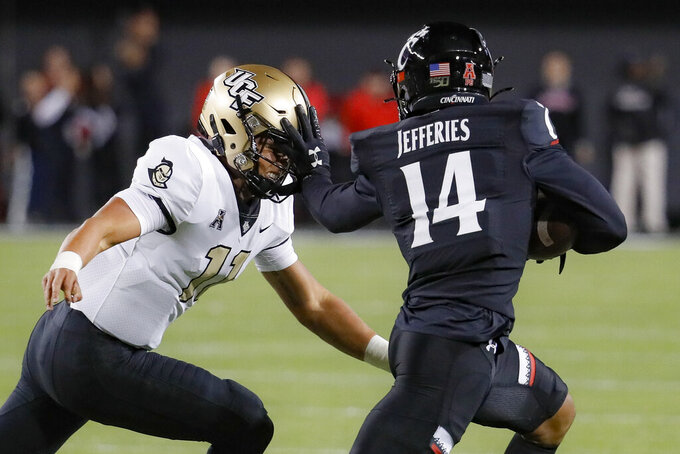 Cincinnati cornerback Cam Jefferies (14) stiff-arms UCF quarterback Dillon Gabriel (11) after intercepting a pass during the first half of an NCAA college football game Friday, Oct. 4, 2019, in Cincinnati. (AP Photo/John Minchillo)