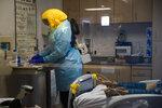 A nurse assists a COVID-19 patient at El Centro Regional Medical Center in El Centro, Calif., Tuesday, July 21, 2020. (AP Photo/Jae C. Hong)