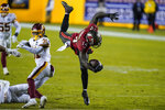 Tampa Bay Buccaneers wide receiver Chris Godwin (14) leaps over Washington Football Team strong safety Kamren Curl (31) during the second half of an NFL wild-card playoff football game, Saturday, Jan. 9, 2021, in Landover, Md. Tampa Bay won 31-23. (AP Photo/Al Drago)