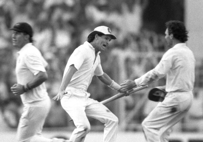 FILE - In this Nov. 8, 1987 file photo, Australian batsman Dean Jones holds the stumps as he races to embrace team captain Allan Border, right, in a moment of jubilation, in Calcutta, India.  Jones has died of an apparent heart attack while in India to commentate on the Indian Premier League, it was reported on Thursday, Sept. 24, 2020. He was 59. Jones represented Australia in 52 tests and 164 one-day internationals. (AP Photo/Liu Heung Shing, File)