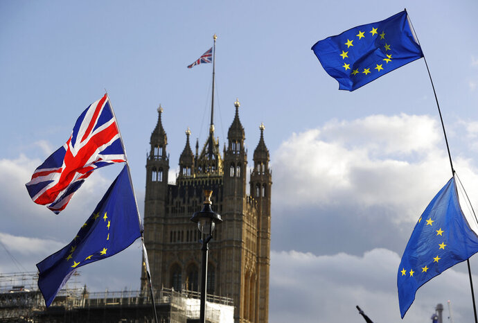 Union Jacks and EU flags fly over Britain's Parliament in London, Saturday, Oct. 19, 2019. In a major blow to British Prime Minister Boris Johnson, U.K. lawmakers voted Saturday to postpone a decision on whether to back his Brexit deal with the European Union, throwing a wrench into government plans to leave the bloc at the end of this month. (AP Photo/Kirsty Wigglesworth)