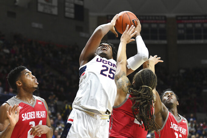 Connecticut's Josh Carlton (25) grabs a rebound against Sacred Heart's Koreem Ozier (2) in the first half of an NCAA college basketball game, Friday, Nov. 8, 2019, in Storrs, Conn. (AP Photo/Stephen Dunn)