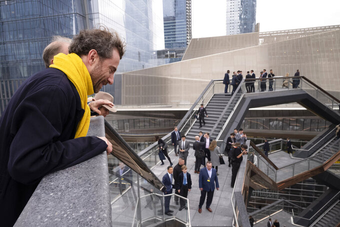 FILE - In this March 15, 2019, file photo, British designer Thomas Heatherwick looks down into the Vessel on its opening day at Hudson Yards in New York.  Officials are evaluating the future of the 150-foot-tall piece of public art in New York City designed by Heatherwick after a string of suicides. Related, a company led by the billionaire Stephen Ross, and Heatherwick's studio had implemented a number of measures at the sculpture intended to prevent deaths. (AP Photo/Mark Lennihan, File)