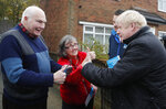 Britain's Prime Minister Boris Johnson, right, speaks to voters, one of which give him a thumbs up, in the Mansfield constituency as he canvases during a General Election campaign trail stop in Mansfield, England, Saturday, Nov. 16, 2019.Britain goes to the polls on Dec.12. (AP Photo/Frank Augstein, Pool)