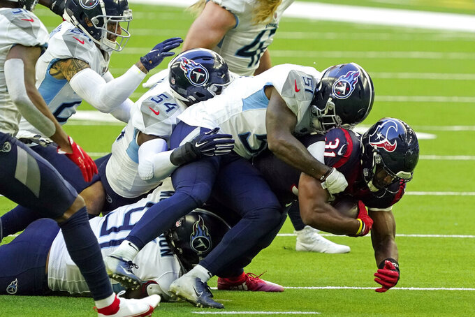 Houston Texans' David Johnson (31) is tackled by Tennessee Titans' David Long Jr. (51), Rashaan Evans (54) and Larrell Murchison (91) during the first half of an NFL football game Sunday, Jan. 3, 2021, in Houston. (AP Photo/Sam Craft)