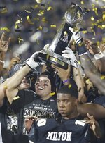 UCF coaches and players celebrate with the championship trophy after an NCAA college football game in the AAC Championship in Orlando on Saturday, Dec. 1, 2018.  (Stephen M. Dowell/Orlando Sentinel via AP)