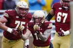 Boston College wide receiver Ben Glines (19) celebrates his touchdown with offensive linemen Chris Lindstrom (75) and Aaron Monteiro (67) during the first half of an NCAA college football game against Louisville in Boston, Saturday, Oct. 13, 2018. (AP Photo/Michael Dwyer)