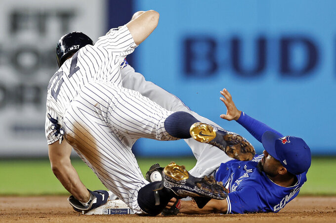 Toronto Blue Jays second baseman Marcus Semien tags out New York Yankees' Giancarlo Stanton (27), who tried to stretch a single into a double during the fourth inning of a baseball game Thursday, Sept. 9, 2021, in New York. Stanton was originally called safe but was called out after a challenge by the Blue Jays. (AP Photo/Adam Hunger)