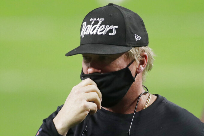 Las Vegas Raiders head coach Jon Gruden wears an Oakland Raiders hat before an NFL football game against the Los Angeles Chargers, Thursday, Dec. 17, 2020, in Las Vegas. (AP Photo/Isaac Brekken)