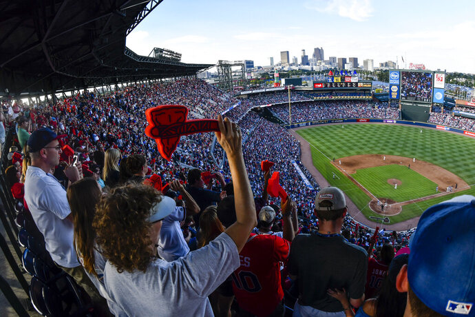 FILe - In this Oct. 2, 2016 file photo, Atlanta Braves fans cheer with a tomahawk chop during the ninth inning of a baseball game against the Detroit Tigers, and the Braves' final game at Turner Field in Atlanta.  Braves officials say they plan to have talks with Native Americans about the Tomahawk Chop chant that has drawn complaints and stoked controversy during the Major League Baseball post-season. The Braves did not distribute their traditional red foam tomahawks to fans before Game 5 of their NL Division Series vs. the St. Louis Cardinals Oct. 9, 2019.  Fans at SunTrust Park raise the tomahawks and thrust them forward in a chopping motion, led by music and graphics on the video boards.  (AP Photo/John Amis, File)
