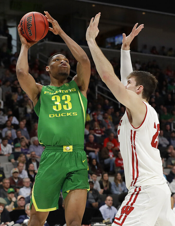 Oregon forward Francis Okoro (33) shoots over Wisconsin forward Ethan Happ during the first half of a first-round game in the NCAA men's college basketball tournament Friday, March 22, 2019, in San Jose, Calif. (AP Photo/Chris Carlson)