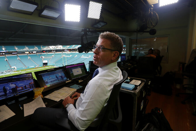 In this Friday, Aug. 23, 2019, photo, Fox Sports analyst Troy Aikman works in the broadcast booth before a preseason NFL football game between the Miami Dolphins and Jacksonville Jaguars, in Miami Gardens, Fla. The exhibition game served as a dress rehearsal for the Fox Sports crew for the upcoming Super Bowl to be hosted by Miami in 2020. (AP Photo/Lynne Sladky)