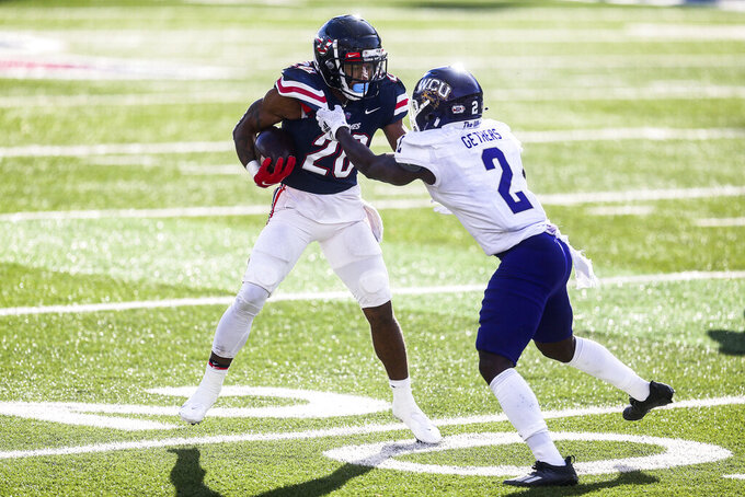 Liberty running back Troy Henderson (20) carries the ball as he is defended by Western Carolina cornerback Aaron Gethers (2) during the second half of an NCAA football game Saturday, Nov. 14, 2020, in Lynchburg, Va. (AP Photo/Shaban Athuman)