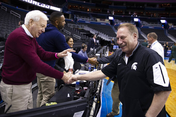 Announcer Bill Raftery, left, greets Michigan State's head coach Tom Izzo during practice at the NCAA men's college basketball tournament in Washington, Thursday, March 28, 2019. Michigan State plays LSU in an East Regional semifinal game on Friday. (AP Photo/Alex Brandon)