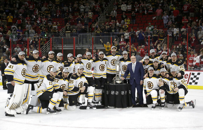Boston Bruins players pose with the Prince of Wales trophy and Bill Daly, deputy commissioner of the National Hockey League, following Game 4 of the NHL hockey Stanley Cup Eastern Conference finals against the Carolina Hurricanes in Raleigh, N.C., Thursday, May 16, 2019. Boston won 4-0 to advance to the Stanley Cup Final. (AP Photo/Gerry Broome)