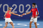 Nina Sojanovic, left, and Novak Djokovic, of Serbia, high five during a first round mixed doubles tennis match against Luisa Stefani and Marcelo Melo, of Brazil, at the 2020 Summer Olympics, Wednesday, July 28, 2021, in Tokyo, Japan. (AP Photo/Patrick Semansky)