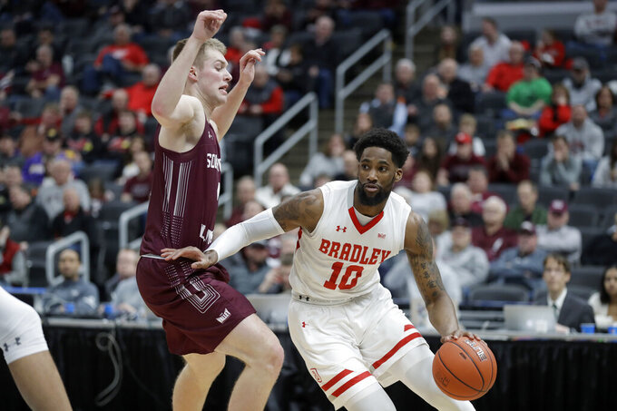 Bradley's Elijah Childs (10) heads to the basket past Southern Illinois' Marcus Domask during the first half of an NCAA college basketball game in the quarterfinal round of the Missouri Valley Conference men's tournament Friday, March 6, 2020, in St. Louis. (AP Photo/Jeff Roberson)