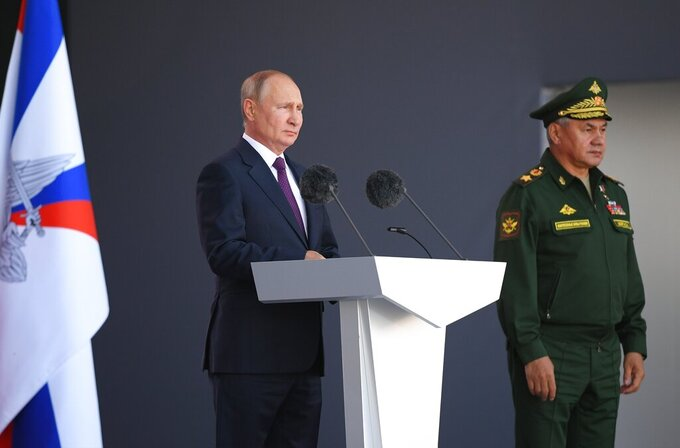 Russian President Vladimir Putin delivers his speech as Russian Defense Minister Sergei Shoigu stands near at the opening ceremony of the International Military Technical Forum Army-2021 in Alabino, outside Moscow, Russia, Monday, Aug. 23, 2021. (Ramil Sitdikov, Sputnik, Kremlin Pool Photo via AP)