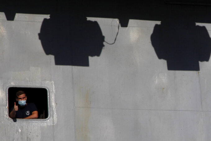 """A French crew member is seen of a window on France's nuclear-powered aircraft carrier Charles de Gaulle at Limassol port, Cyprus, Monday, May 10, 2021. With the Task Force's deployment on its mission named """"Clemenceau 21,"""" France is assisting in the fight against terrorism while projecting its military power in regions where it has vital interests. (AP Photo/Petros Karadjias)"""