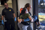 In this photo taken June 8, 2019, as Brian Butkiewicz watches, Frances Roberts, a Carson, Calif., public safety employee, carries a victim with a simulated leg injury during a disaster training scenario. As police and firefighter numbers dwindle, authorities urge personal responsibility. (Brigette Waltermire/News21 via AP)