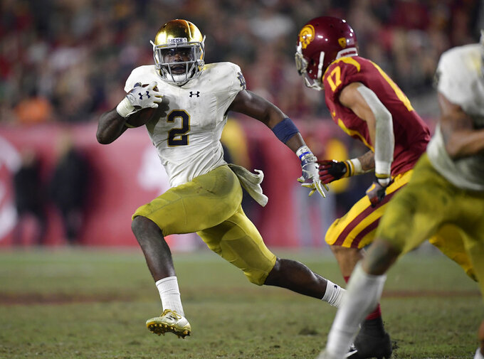 Notre Dame running back Dexter Williams, left, carries the ball as Southern California cornerback Chase Williams defends during the second half of an NCAA college football game Saturday, Nov. 24, 2018, in Los Angeles. Notre Dame won 24-17. (AP Photo/Mark J. Terrill)