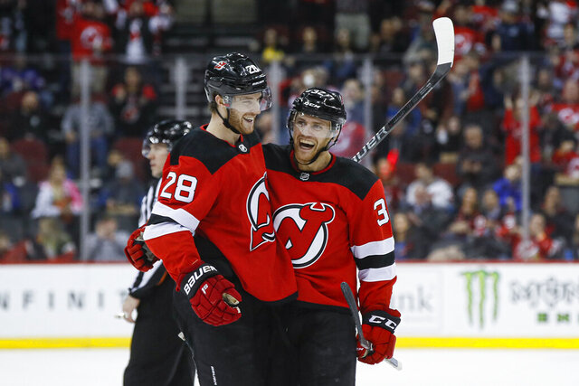 =New Jersey Devils defenseman Dakota Mermis, right, celebrates with defenseman Damon Severson (28) after scoring against St. Louis Blues goaltender Jordan Binnington during the second period of an NHL hockey game, Friday, March 6, 2020, in Newark. (AP Photo/John Minchillo)