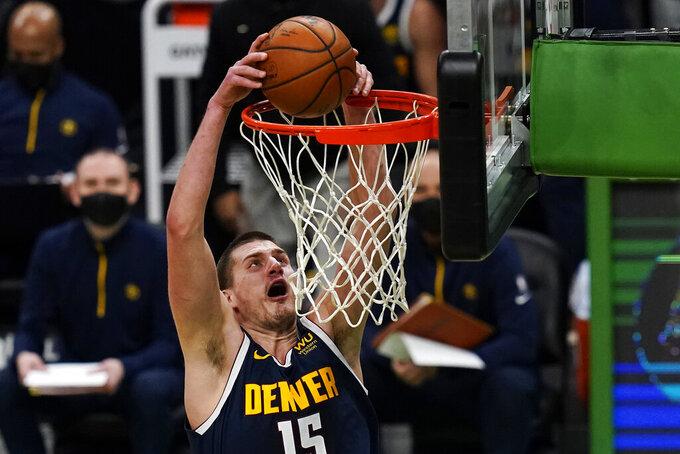 Denver Nuggets center Nikola Jokic (15) slams a dunk against the Boston Celtics during the first half of an NBA basketball game, Tuesday, Feb. 16, 2021, in Boston. (AP Photo/Charles Krupa)