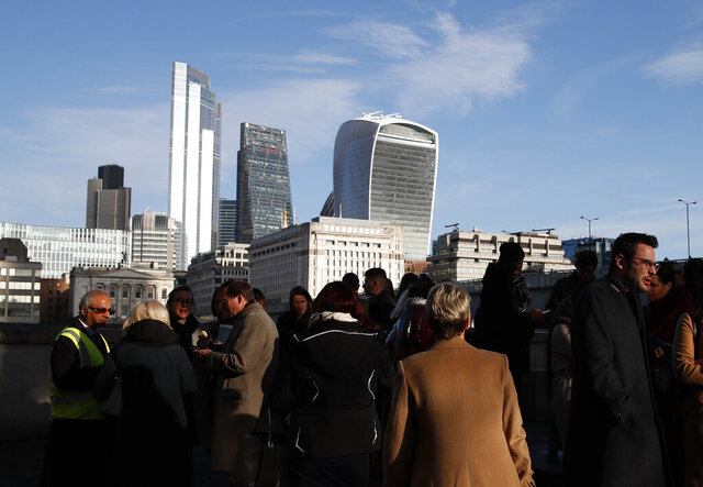 FILE - In this file photo dated Wednesday, Dec. 11, 2019, people gather near London Bridge, backdropped by the city of London financial district, with 20 Fenchurch Street building known as The Walkie-Talkie building, top right.  Prime Minister Boris Johnson's decisive victory in last week's general election provided little comfort to Britain's once world-beating financial services industry, which has been battered by Brexit for more than three years. (AP Photo/Thanassis Stavrakis, FILE)