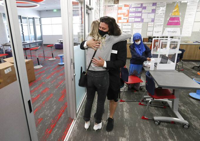 John Arthur, Utah's Teacher of the Year, hugs his wife, Stacey, in his classroom at Meadowlark Elementary School in Salt Lake City after learning of the award on Thursday, Oct. 1, 2020. Now in his eighth year of teaching, Arthur teaches sixth grade at Meadowlark Elementary School, a Title I school in the Salt Lake City School District. It is there that he pays it forward, helping his students learn to advocate for children and immigrants through music videos that they produce together and share on their YouTube channel, 9thEvermore. Arthur's students have received national recognition for their work. (Steve Griffin/The Deseret News via AP)