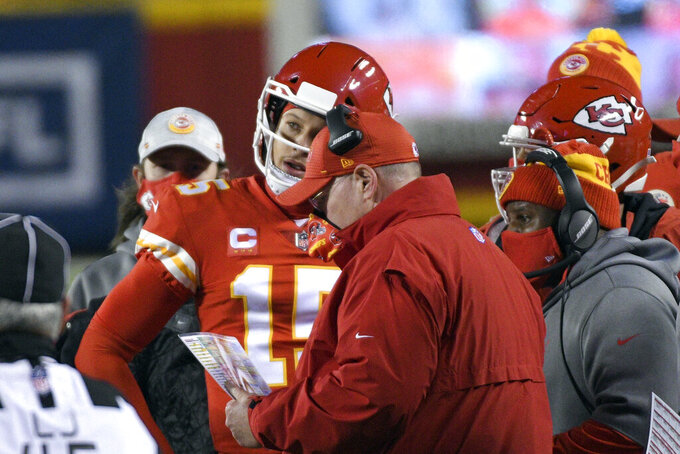 Kansas City Chiefs quarterback Patrick Mahomes talks with head coach Andy Reid during the first half of the AFC championship NFL football game against the Buffalo Bills, Sunday, Jan. 24, 2021, in Kansas City, Mo. (AP Photo/Reed Hoffmann)