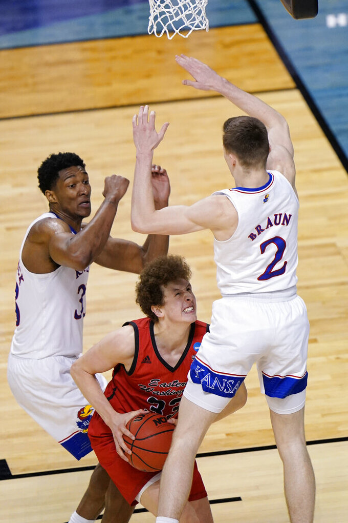 Eastern Washington guard Jacob Groves (33) is pressured by Kansas forward David McCormack, left, and teammate Christian Braun (2) as he get up for a shot during the second half of a first-round game in the NCAA college basketball tournament at Farmers Coliseum in Indianapolis, Saturday, March 20, 2021. (AP Photo/AJ Mast)