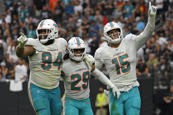 Miami Dolphins defensive end Christian Wilkins (94) and linebacker Jaelan Phillips (15) react after defensive back Brandon Jones (29) sacked Las Vegas Raiders quarterback Derek Carr (4) during the second half of an NFL football game, Sunday, Sept. 26, 2021, in Las Vegas. (AP Photo/David Becker)