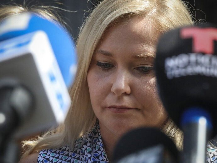 In this Aug. 27, 2019, photo, Virginia Roberts Giuffre, who says she was trafficked by sex offender Jeffrey Epstein, holds a news conference outside a Manhattan court where sexual assault claimants invited by a judge addressed a hearing following Epstein's jailhouse death in New York. Prince Andrew suffered fresh scrutiny Monday night, Dec. 2, when the woman who says she was a trafficking victim made to have sex with him when she was 17 asked the British public to support her quest for justice. (AP Photo/Bebeto Matthews)