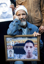 A Tunisian man hold the picture of his son who died seven years ago during revolution at a rally in Tunis, Tunisia, Sunday, Jan. 14, 2018. Tunisian authorities announced plans to boost aid to the needy in a bid to placate protesters whose demonstrations over price hikes degenerated into days of unrest across the North African nation, which is marking seven years on Sunday since its long-time autocratic ruler was driven into exile. (AP Photo/Hassene Dridi)