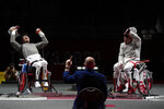 China's Feng Yanke, left, reacts as he won a gold medal a gold medal in men's sabre individual category B against Poland's Adrian Castro at the Tokyo 2020 Paralympic Games, Wednesday, Aug. 25, 2021, in Chiba, Japan. (AP Photo/Kiichiro Sato)