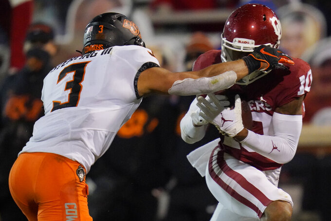 Oklahoma wide receiver Theo Wease (10) takes a pass into the end zone in front of Oklahoma State safety Tre Sterling (3) for a touchdown during the second half of an NCAA college football game in Norman, Okla., Saturday, Nov. 21, 2020. (AP Photo/Sue Ogrocki)