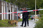 Forensic experts with a dog search for evidence in the area where a lawyer who represented a key witness in a major Dutch organized crime trial was gunned down in Amsterdam, in Amsterdam, Netherlands, Wednesday, Sept. 18, 2019. Police said that 44-year-old lawyer Derk Wiersum was fatally shot Tuesday morning by a man who fled on foot and was still being hunted. (AP Photo/Peter Dejong)