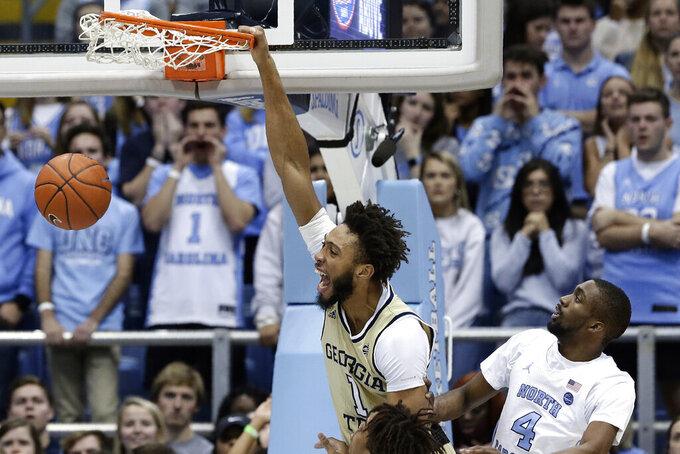 Georgia Tech forward James Banks III (1) dunks next to North Carolina guard Brandon Robinson (4) during the first half of an NCAA college basketball game in Chapel Hill, N.C., Saturday, Jan. 4, 2020. (AP Photo/Gerry Broome)