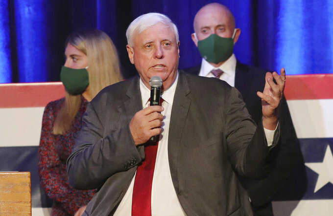FILE - In this Nov. 3, 2020, file photo, West Virginia Gov. Jim Justice celebrates his reelection at The Greenbrier Resort in White Sulphur Springs, W.Va. A federal judge on Wednesday, July 21, 2021, blocked West Virginia from enforcing a new ban on transgender athletes. The law, signed by Justice in April, would prohibit transgender athletes from competing in female sports in middle and high schools and colleges. (AP Photo/Chris Jackson, File)