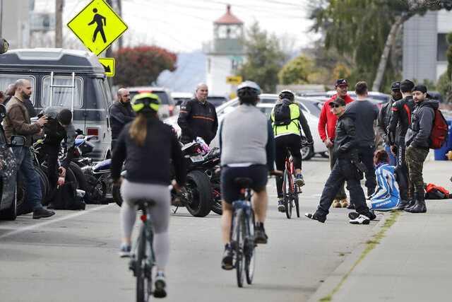 Bicyclists wind through a group gathered along a path at Alki Beach Park Sunday, March 22, 2020, in Seattle, where people are asked to maintain a physical distance of at least six feet apart in response to the coronavirus outbreak. Health officials reported Sunday that there have been at least 95 coronavirus deaths in Washington state and nearly 2,000 confirmed cases. (AP Photo/Elaine Thompson)
